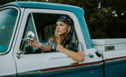 Une femme avec un Bandana au volant de sa voiture